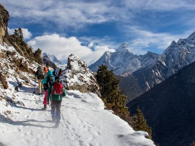 Trekkers hiking through the snow in the Himalayas